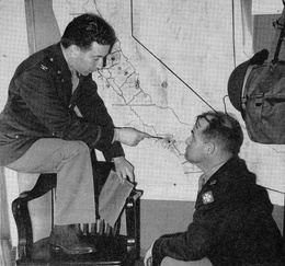 Karl Bendetsen (left) pointing out  				a feature on the map of the Pacific Coast areas with  				Stanford grad, Hugh Fullerton (right), at right, served  				on Bendetsen's staff, c. Jul. 1942, California. Courtesy  				of the Karl R. Bendetsen Papers, Hoover Institution  				Archives
